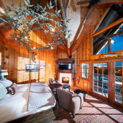 cozy cabin-like bedroom with fireplace and balcony